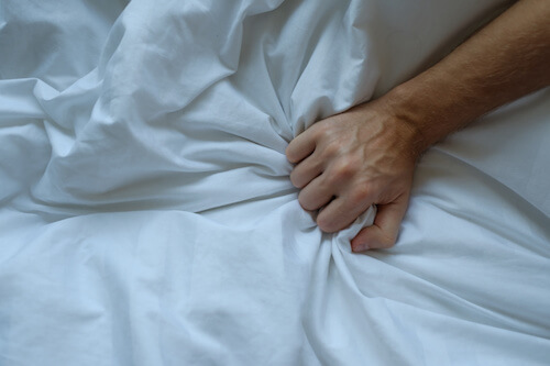 Caucasian man hand grasping on bed. He is alone in bed