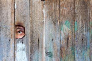 Oog van voyeur spiekt door een gat in de schutting